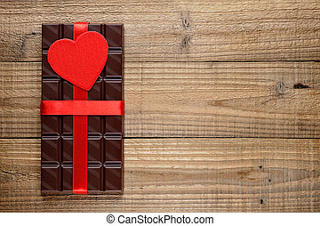 Chocolate with red heart on wooden background