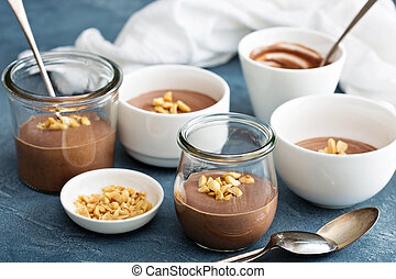Chocolate yogurt dessert with salted peanuts in cups