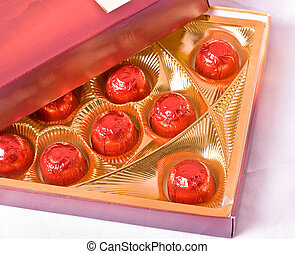 chocolates candy in red foil, in a box