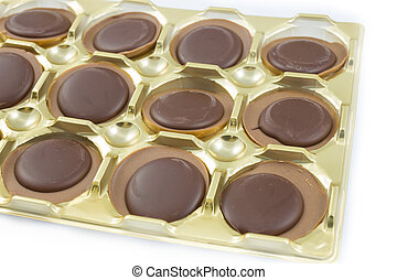Chocolates in a gold box on white background