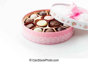 Chocolates in pink box on white background