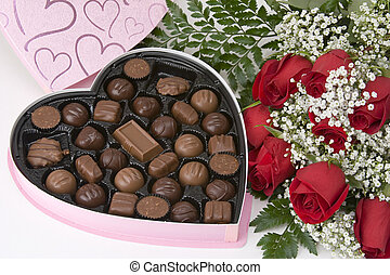 Picture of a dozen Red Roses on white background with Heart Shaped Box of Chocolates