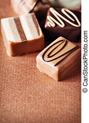 Chocolates - Pralines on brown background, shallow DoF
