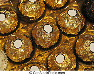 Chocolates with round shape in golden foil and white labels