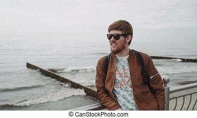 chodząc, brązowy, uśmiecha się, plecak, broda, modny, skórzana marynarka, młody, spojrzenia, morze, sunglasses, czerwony, człowiek