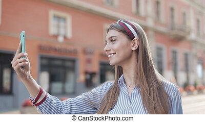 chodząc, kaukaski, kapitałka, używając, concept., koszula, ładna dziewczyna, ulica., komunikacja, młody, pasiasty, to, telefon, reputacja, miasto, jej, ruchomy, ustalać, video, uśmiechanie się, rozmowa telefoniczna