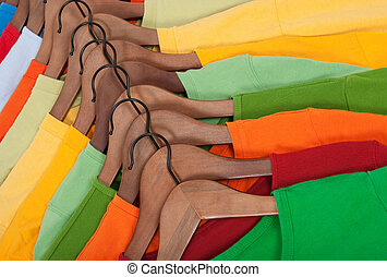 Choice of colorful t-shirts on wooden hangers