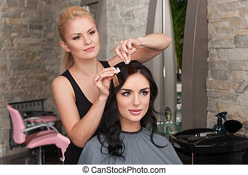 Choice of tone of hair in hair salon. Female client and hairdresser choosing shades of colour in salon