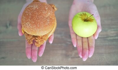 Choose between a calorie burger and a green apple. Women's hands hold harmful and healthy food slowmo