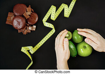 Choose between sweets and fruits. Diet concept, overweight. Weight loss and diabetes.
