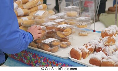 choose fresh baked goods in the supermarket - people choose...
