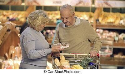 Choosing a Cake - Close up of mature couple choosing a cake...