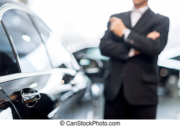 Choosing a car at dealership. Thoughtful grey hair man in...