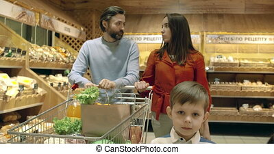 Choosing Bread - Adult couple with two kids shopping for...