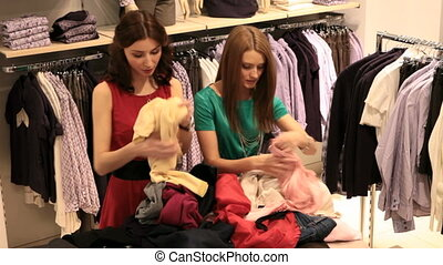 Choosing clothes - Two girls choosing clothes in the store