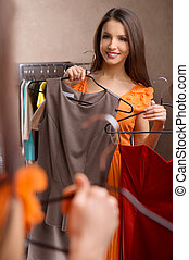 Choosing dress. Attractive young woman holding dresses in her hands and looking at the mirror