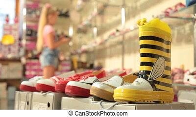 Choosing Footwear in Shoe Store - Little girl choosing...