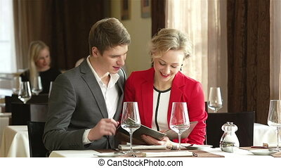 Choosing From Menu - Lovely young people choosing from a...