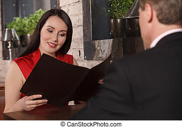 Choosing from the Menu. Beautiful middle-aged women reading Menu while sitting at the restaurant with her boyfriend