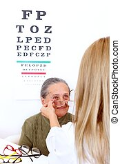 Choosing glasses at the optician - Elderly woman choosing a...