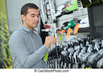 choosing golf club on retail shop