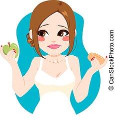 Sad young woman choosing healthy green apple instead of sweet doughnut