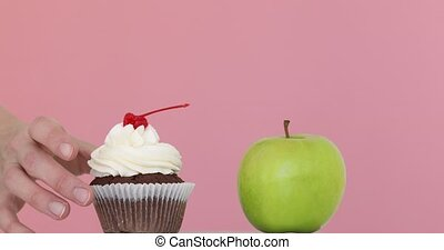 Choosing healthy diet - Hand takes apple cake remains table