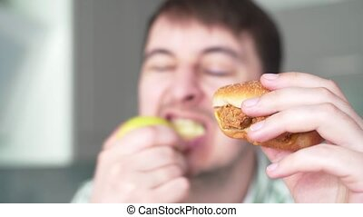 Choosing healthy or unhealthy food. Hungry man bites apple on the background cheeseburger slow motion