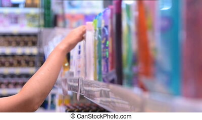 Choosing shampoo in the store - Close-up shot of a woman...
