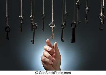 Choosing the right one - Hand choosing a hanging key amongst...
