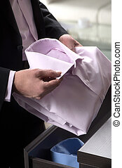 Choosing the right shirt. Close-up of businessman holding a shirt in his hands