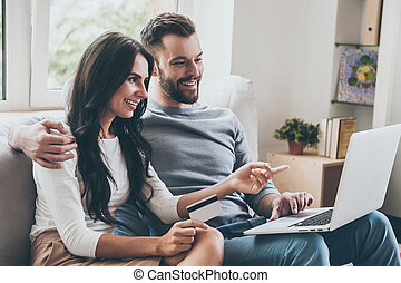 Choosing what to get. Beautiful young woman holding credit card and pointing laptop with smile while sitting together with her husband on the couch