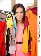 Choosing what to wear. Beautiful young woman holding dresses in her hands and smiling at camera