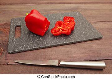 Chopped bellpepper on cutting board and knife on wooden table