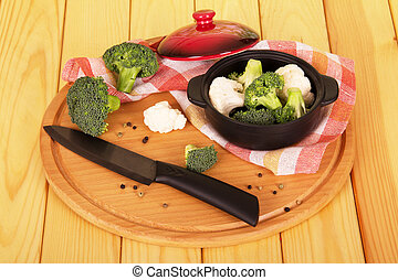 Chopped cauliflower in bowl and knife on wooden table -...