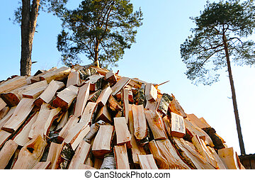 chopped firewood pile - chopped pine firewood pile on blue...