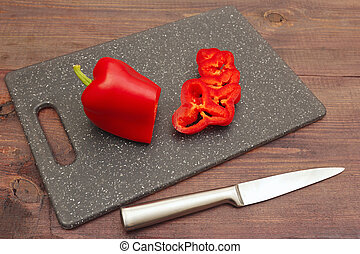 Chopped fresh bellpepper on cutting board and knife on wooden table