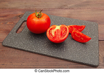 Chopped fresh tomato on cutting board on wooden table