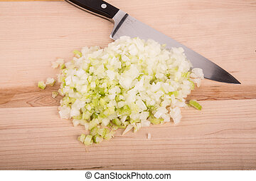 Chopped Onions and Celery on Board with Knife