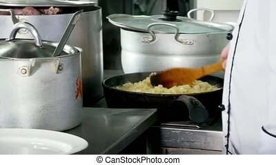 Chopped onions fried in vegetable oil in the pan in the...