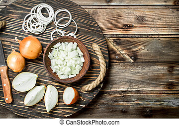 Chopped onions in a bowl and pieces of onions on the tray with a knife.