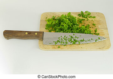 chopped parsley on cutting board with knife