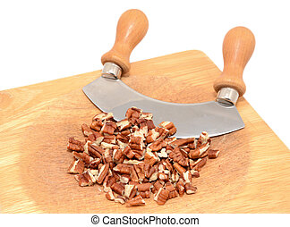 Chopped pecan nuts with a rocking knife on a wooden chopping...