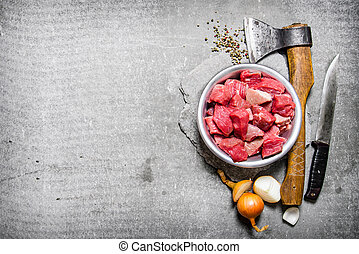 Chopped raw meat with an axe, cutting knife and spices. On...