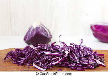 Chopped red cabbage on cutting board, closeup. Side view.