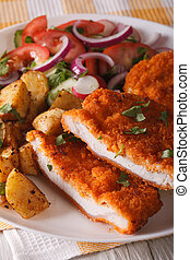Chopped schnitzel, salad and fried potatoes close-up. vertical