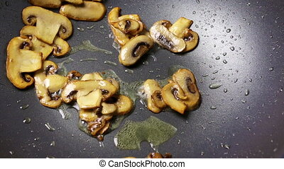Chopped slices of mushrooms and chicken fillets are fried in an oil in a wok pan. Part of the process of cooking with champignons in the home recipe. Close