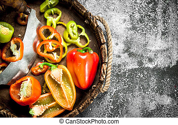 chopped sweet pepper in a wooden tray with a knife.