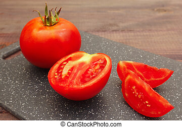 Chopped tomato on cutting board on wooden table