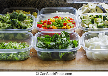 Chopped vegetables in plastic storage containers ready for cooking or storage.